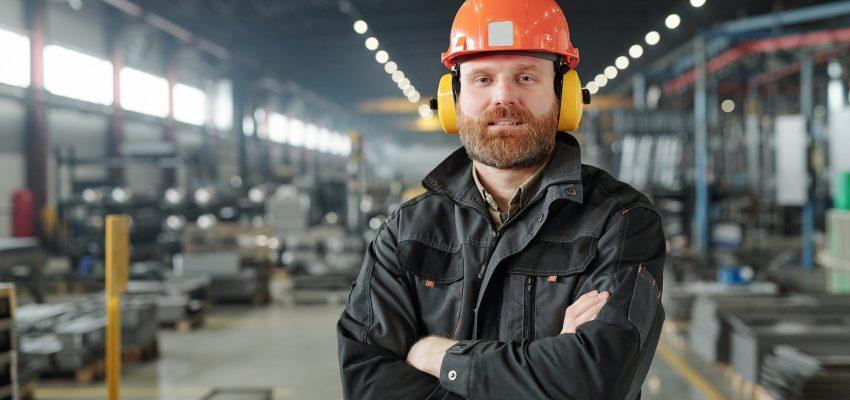 Bearded factory worker in ear protectors
