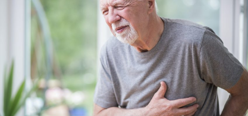 Senior grey man home alone having a heart attack